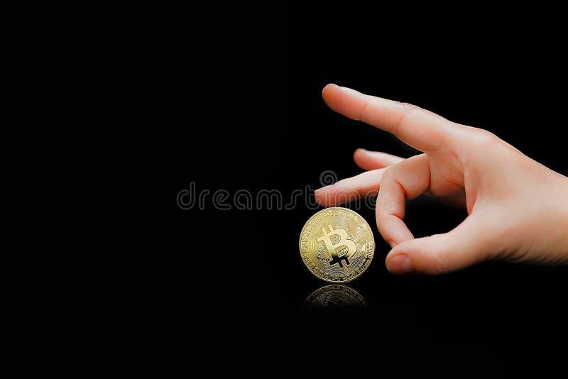 Os dedos da mulher jogam para fora o bitcoin Bitcoins em um fundo preto Bitcoins e conceito virtual novo do dinheiro Bitcoin é um fotografia de stock royalty free