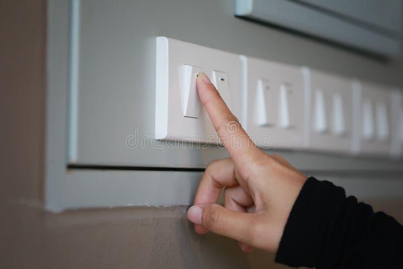 os dedos estão desligando o interruptor da luz na casa fotografia de stock royalty free