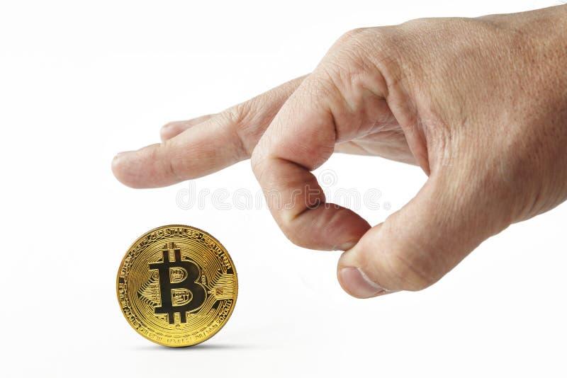 Os dedos masculinos empurram o bitcoin dourado afastado em um fundo branco A mão do homem isolado que joga o cryptocoin sem valor imagens de stock