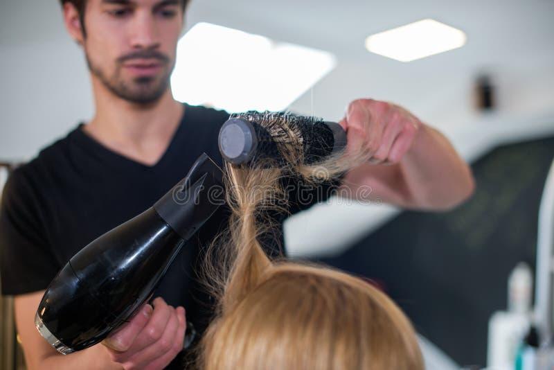 OS del parrucchiere che asciuga i giovani capelli biondi della donna fotografie stock libere da diritti