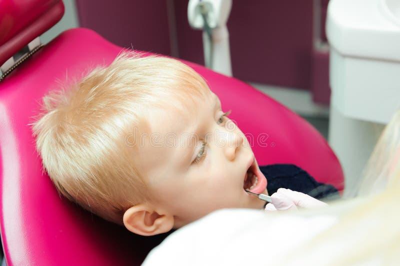 Os dentes da criança de exame do dentista na clínica dental fotografia de stock royalty free