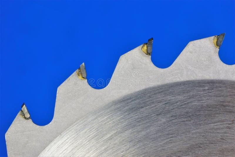 Os dentes da l?mina de serra em um fundo azul, close-up Circular viu - a ferramenta de corte sob a forma de um disco liso do meta foto de stock royalty free