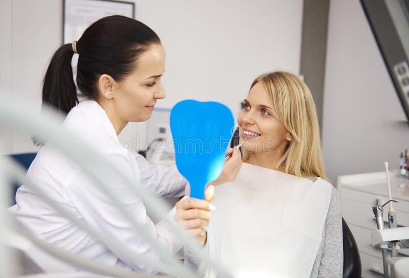 Os dentes da mulher de exame do stomatologist alegre fotos de stock royalty free