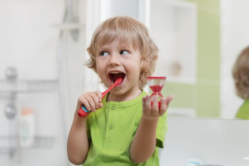 Os dentes de escovadela da criança feliz aproximam o espelho no banheiro Está monitorando a duração da ação de limpeza com ampulh imagem de stock royalty free