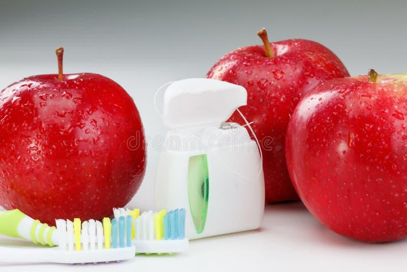 Os dentes dentais floss, escova de dentes e maçã vermelha imagens de stock royalty free