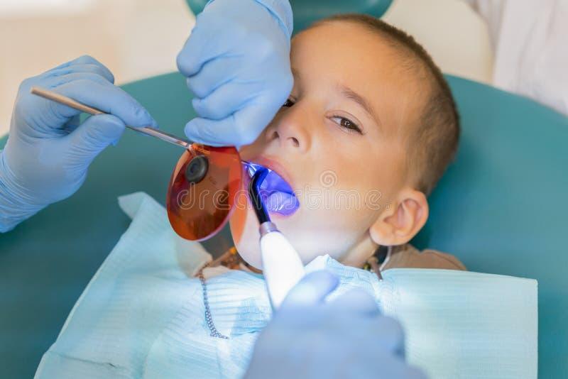 Os dentes do menino de exame do dentista na cl?nica Um paciente pequeno na cadeira dental sorri Dantist trata os dentes Feche aci fotografia de stock royalty free