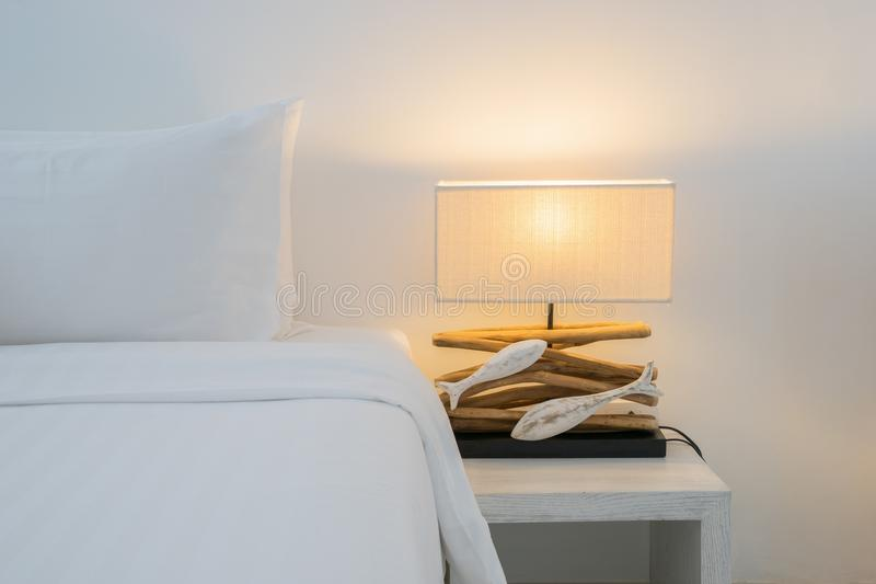 Os descansos no estilo da lâmpada da cama e do luxo no lado de madeira da tabela no quarto projetam, estilo do processo do vintag imagem de stock