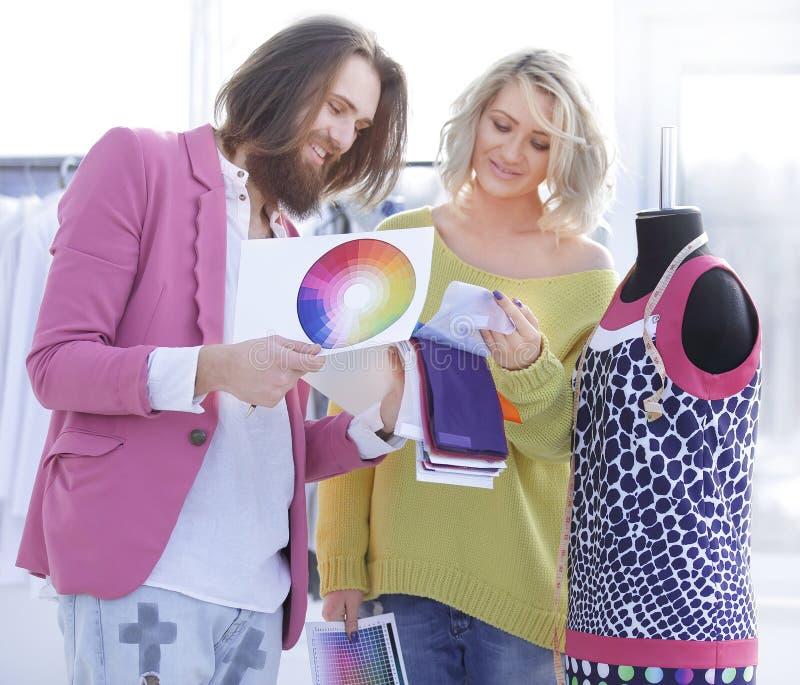 Os desenhadores de moda discutem a tela e a cor da cole??o nova da roupa fotos de stock