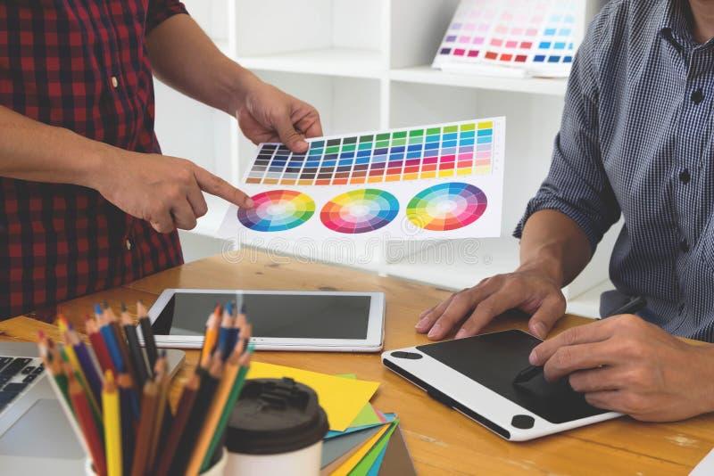 Os designer gráficos apresentam cores da paleta de cores a seus amigos, para ideias criativas do projeto, projetos criativos do g foto de stock
