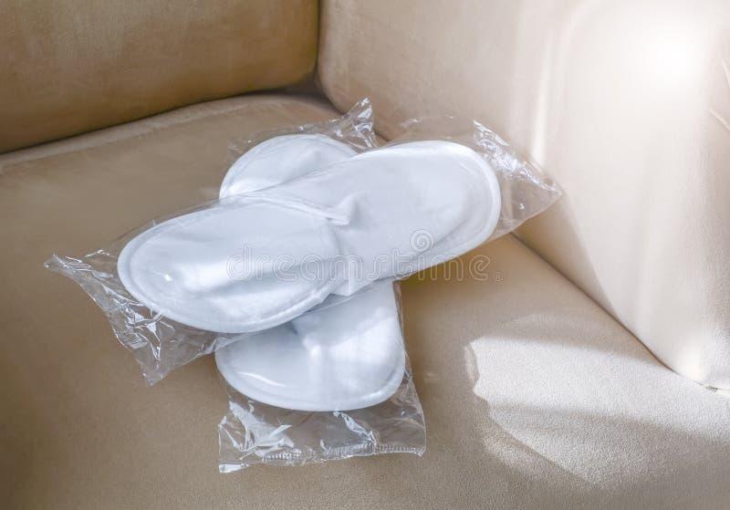 Os deslizadores descartáveis brancos novos em um pacote transparente encontram-se na poltrona em uma sala de hotel foto de stock royalty free