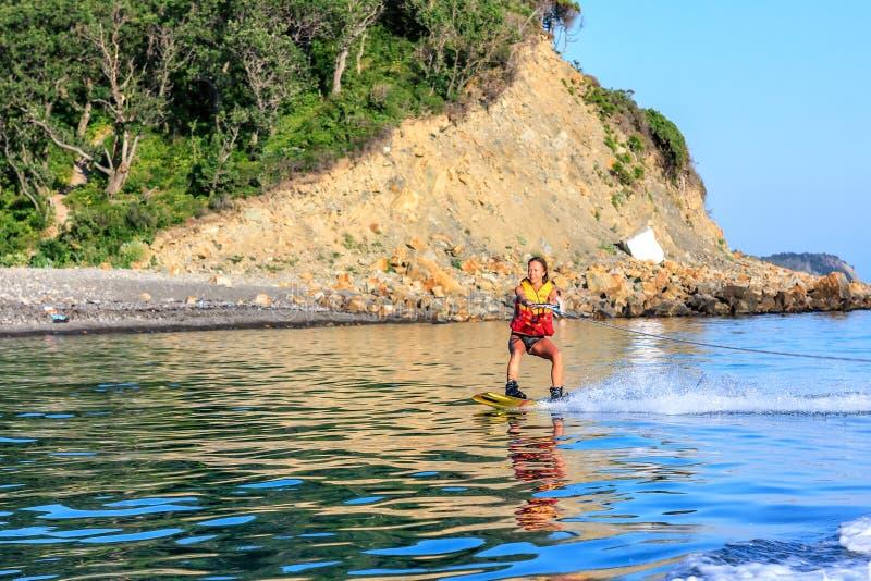 Os deslizes do wakeboarder da jovem mulher no mar liso surgem após o barco de motor ao longo da linha costeira rochosa no por do  fotografia de stock