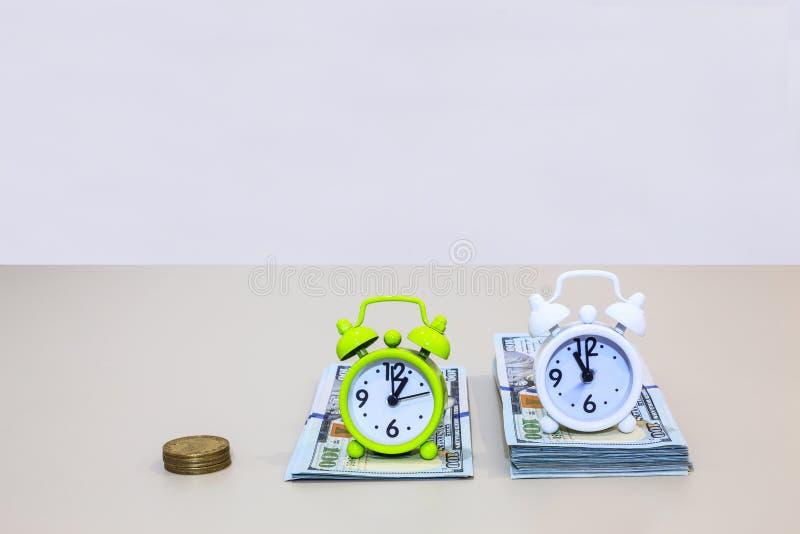Os despertadores em pilhas do dinheiro do dólar americano referem Tempo é dinheiro a frase Conceito do negócio e da finança imagens de stock
