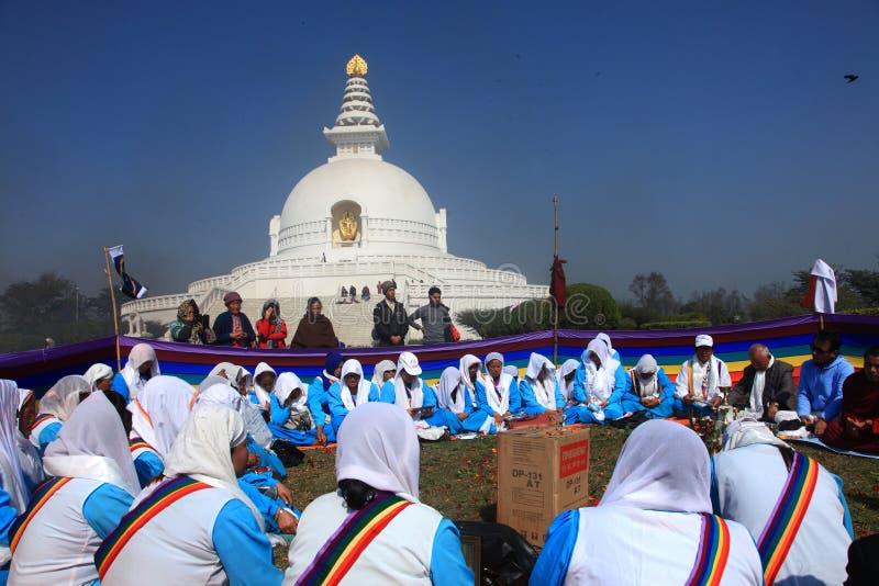 Os devotos budistas no grupo oferecem orações religiosas na frente do pagode da paz de mundo imagens de stock