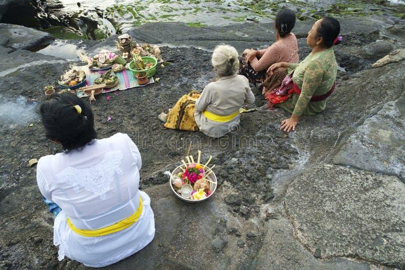 Os devotos hindu do Balinese rezam no por do sol imagens de stock