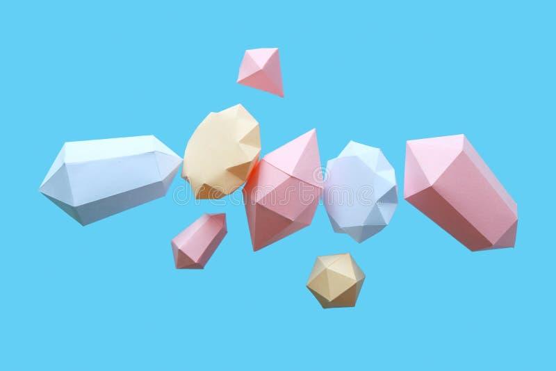 Os diamantes poligonais fizeram do papel em um fundo azul fotografia de stock