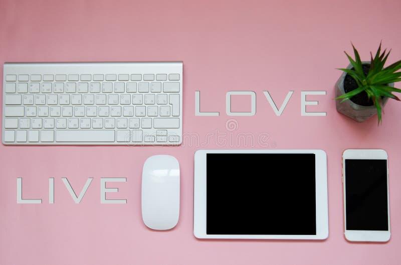 Os dispositivos brancos no fundo cor-de-rosa com amor vivem sinal Zombaria acima foto de stock