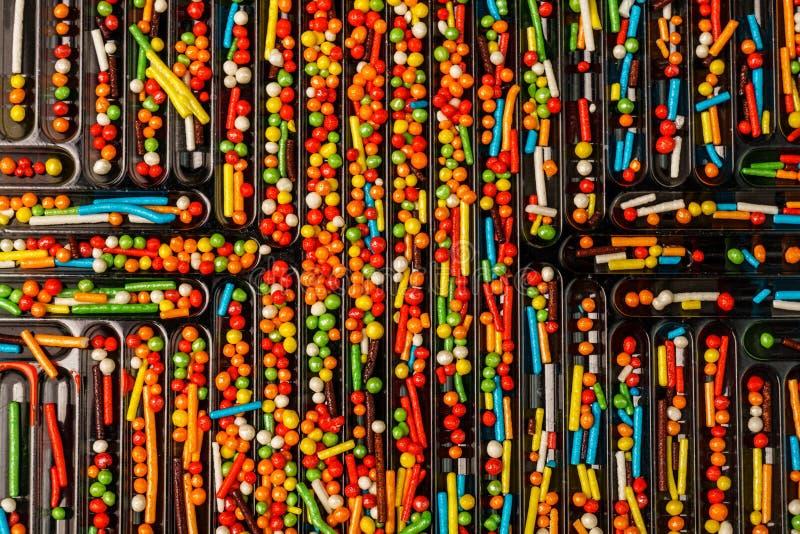 Os doces coloridos polvilham são arranjados em pilhas da bandeja para o uso como t imagem de stock royalty free