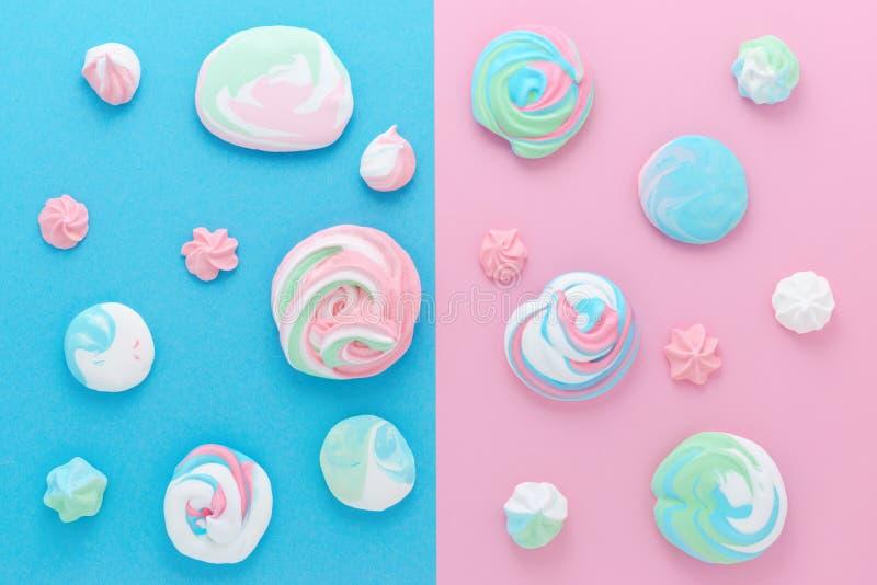 Os doces cor-de-rosa e azuis, merengues nas cores pastel, modelam o sumário foto de stock
