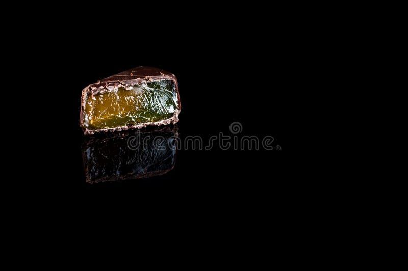 Os doces da geleia da cor verde e amarela doused com chocolate em um fundo preto, isolado fotos de stock