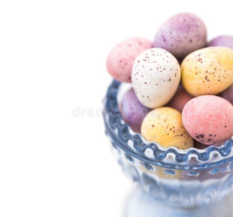 Os doces de chocolate salpicaram ovos da páscoa coloridos nas cores pastel no copo de cristal azul no fundo branco fotos de stock royalty free