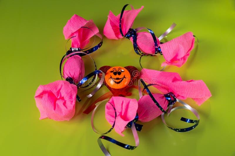 Os doces três envolvidos grandes no papel cor-de-rosa com fita azul, sorriso engraçado no coração vermelho estão no fundo/tabela  fotografia de stock royalty free