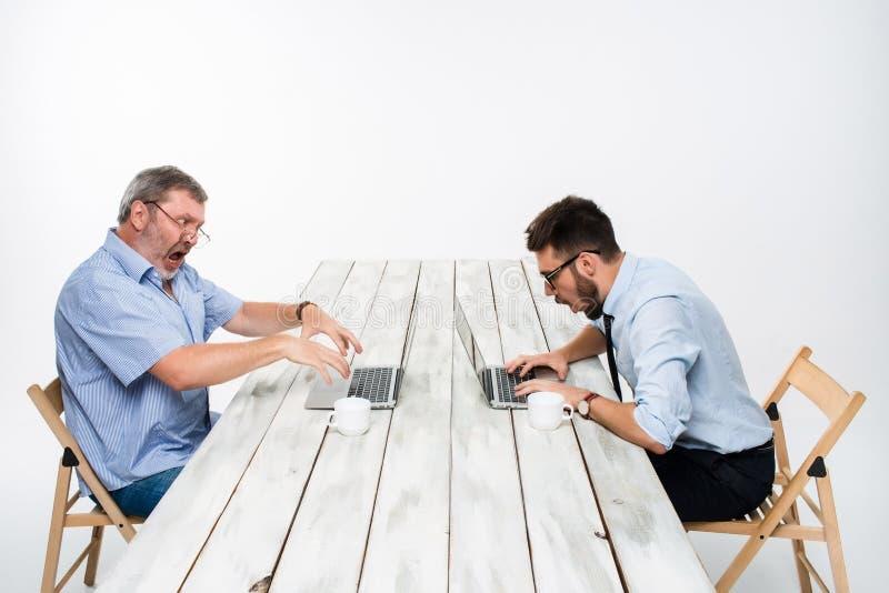 Os dois colegas que trabalham junto no escritório no fundo branco fotos de stock royalty free