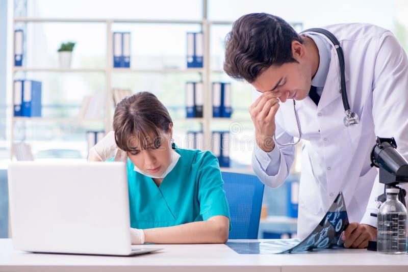 Os dois doutores que discutem a imagem do mri do raio X no hospital foto de stock royalty free