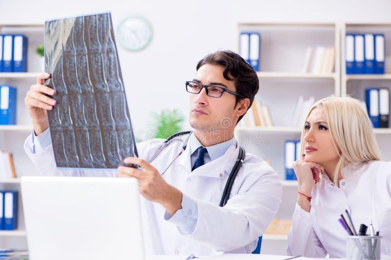 Os dois doutores que examinam imagens do raio X do paciente para o diagnóstico fotos de stock royalty free