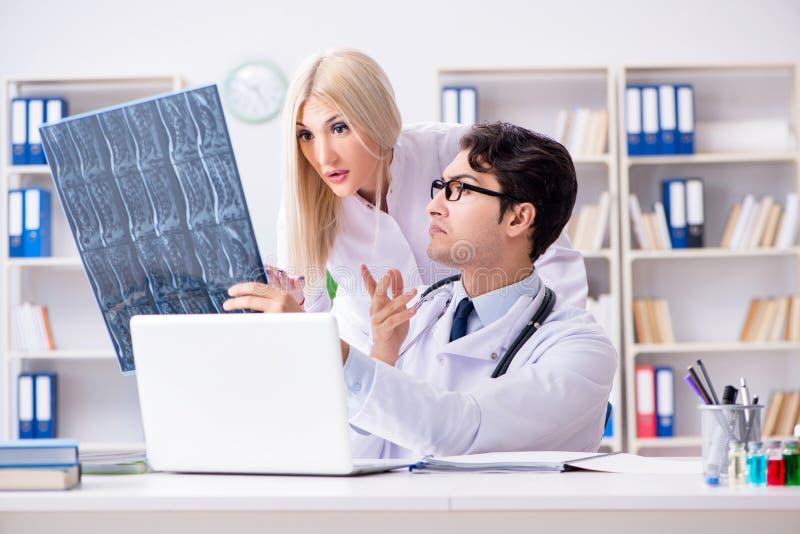 Os dois doutores que examinam imagens do raio X do paciente para o diagnóstico imagens de stock