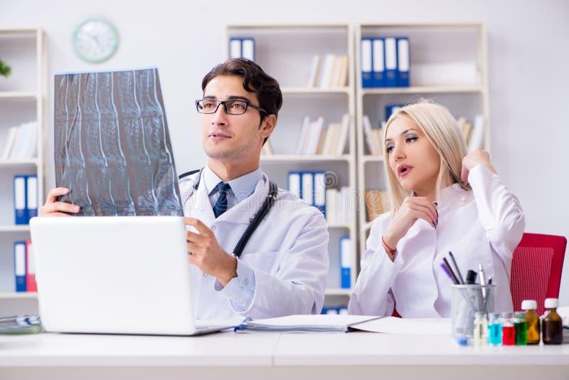 Os dois doutores que examinam imagens do raio X do paciente para o diagnóstico fotografia de stock royalty free