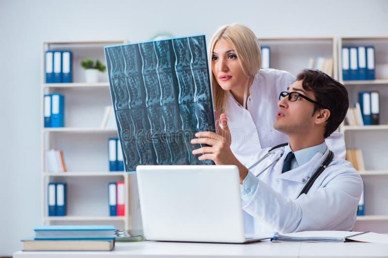 Os dois doutores que examinam imagens do raio X do paciente para o diagnóstico foto de stock royalty free