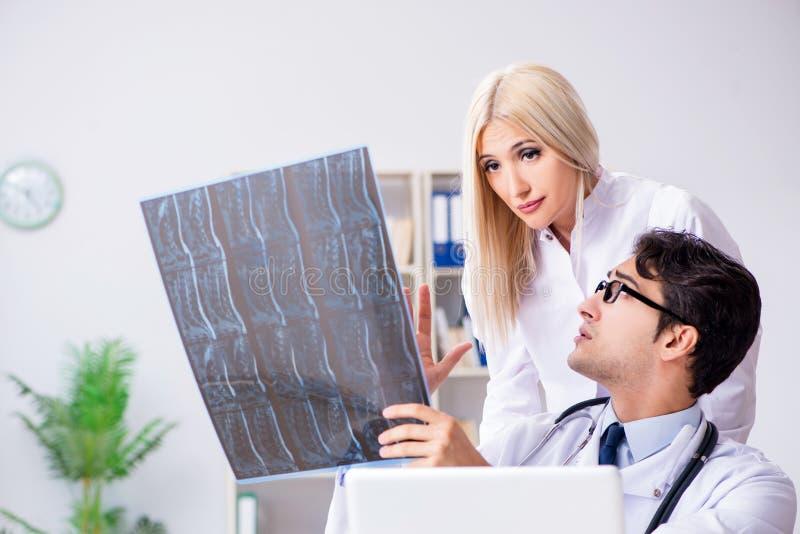 Os dois doutores que examinam imagens do raio X do paciente para o diagnóstico imagens de stock royalty free