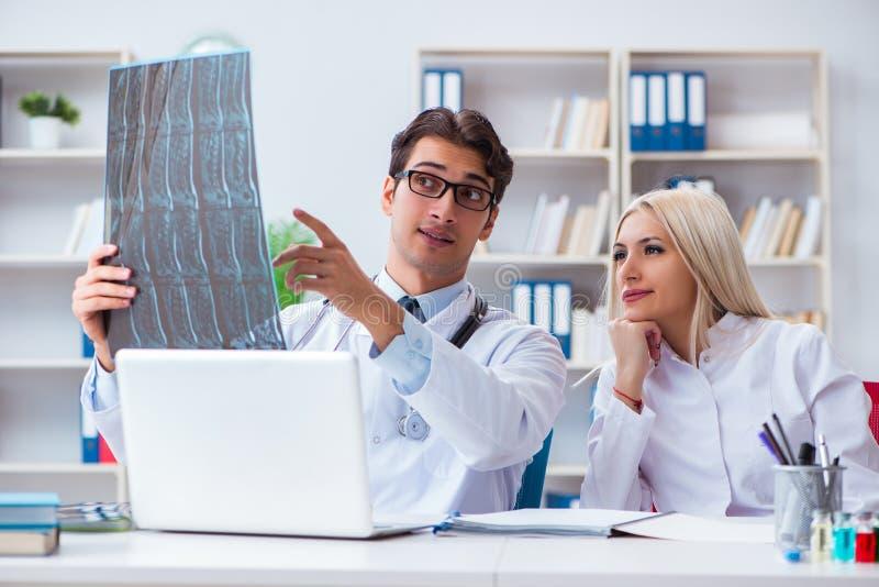 Os dois doutores que examinam imagens do raio X do paciente para o diagnóstico foto de stock