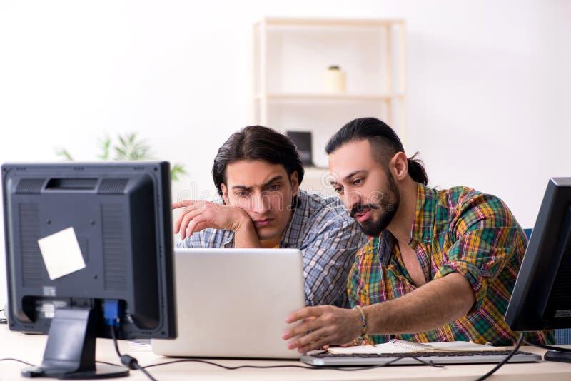 Os dois ele especialistas que trabalham no escrit?rio fotos de stock