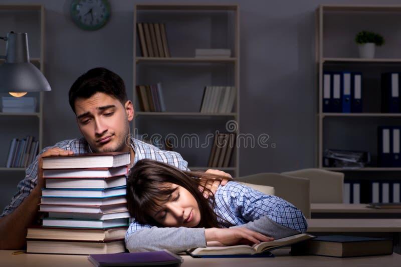 Os dois estudantes que estudam tarde na noite foto de stock