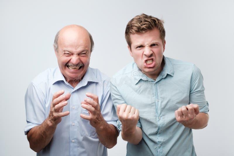 os dois homens irritados exclamam com grito negativo das emoções alto, sobre a parede branca do estúdio O filho e o pai irritados imagens de stock