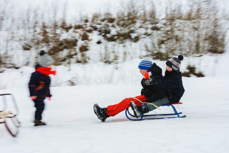 Os dois meninos descem em pequenos trenós, e a menina espera-os, seu movimento é visível imagens de stock