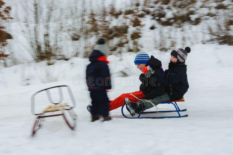Os dois meninos descem em pequenos trenós, e a menina espera-os, seu movimento é visível imagens de stock royalty free