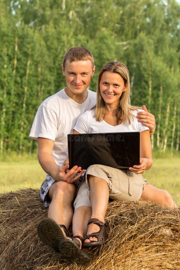 Os dois povos bonitos no monte de feno olham o Internet fotografia de stock