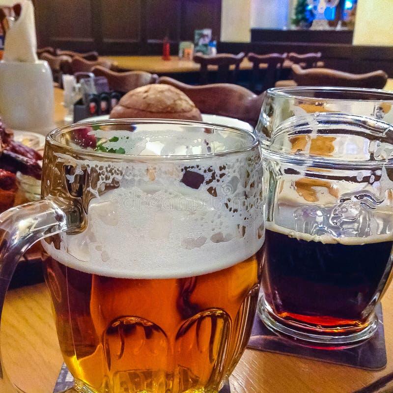 Os dois vidros da cerveja checa em uma tabela de madeira do tambor imagens de stock