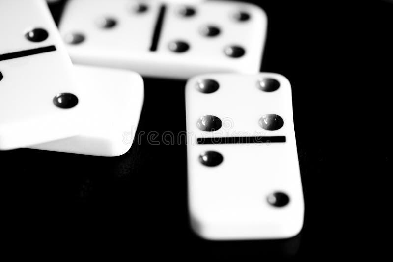 Os dominós são dispersados em uma superfície escura Rebecca 36 fotografia de stock royalty free