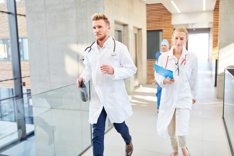 Os doutores do grupo estão correndo rapidamente em uma emergência fotos de stock