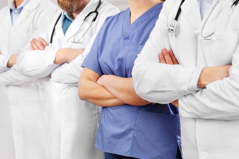Os doutores e as enfermeiras na equipe dos cuidados médicos com braços cruzaram-se em seguido no hospital fotos de stock