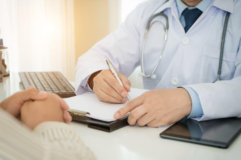Os doutores e o paciente do homem estão discutindo algo para o consultatio fotos de stock royalty free