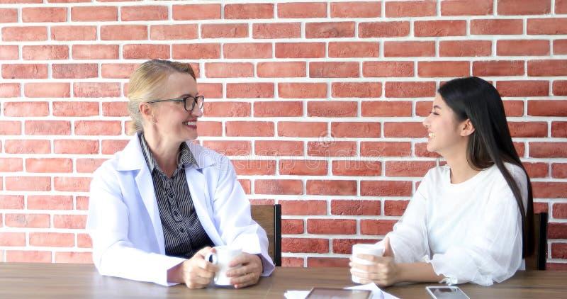 Os doutores estão bebendo o café e a feliz de sorriso e de riso imagens de stock