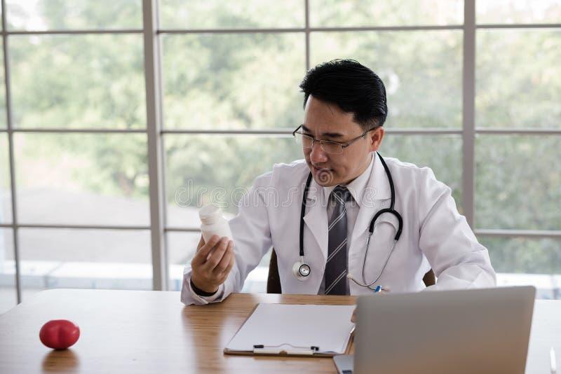 Os doutores, homens estão lendo etiquetas em garrafas da medicina à disposição Em fotografia de stock