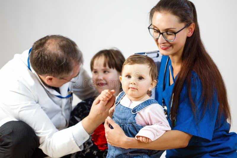 Os doutores jogam com duas jovens crianças foto de stock royalty free