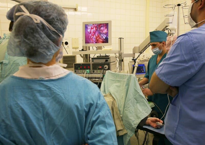 Os doutores observam um curso da operação laparoscopic complexa imagens de stock royalty free