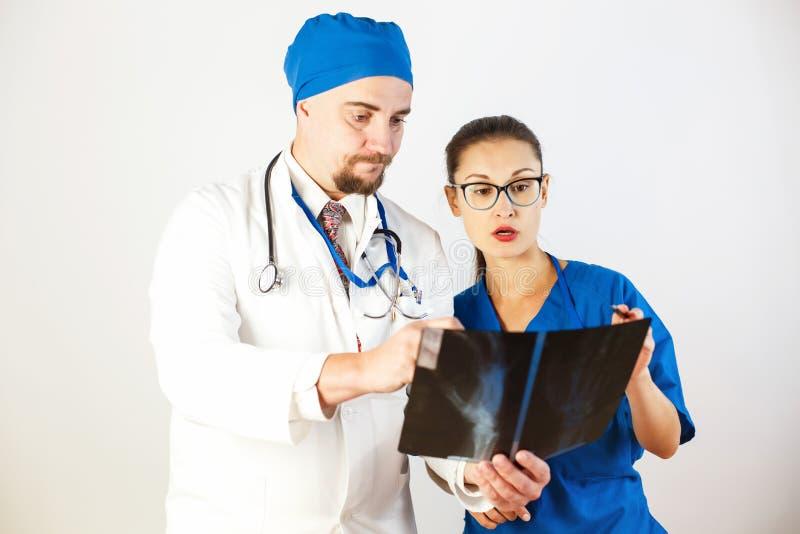 Os doutores olham o raio X, veem o problema e discutem-no Fundo branco foto de stock royalty free