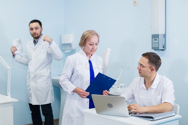 Os doutores sérios maduros bonitos estão usando um portátil, discutindo o diagnóstico ao estar na clínica fotografia de stock royalty free